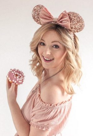 Denise Joanne, the owner of this blog, smiling with pink Minnie Mouse ears and a donut.