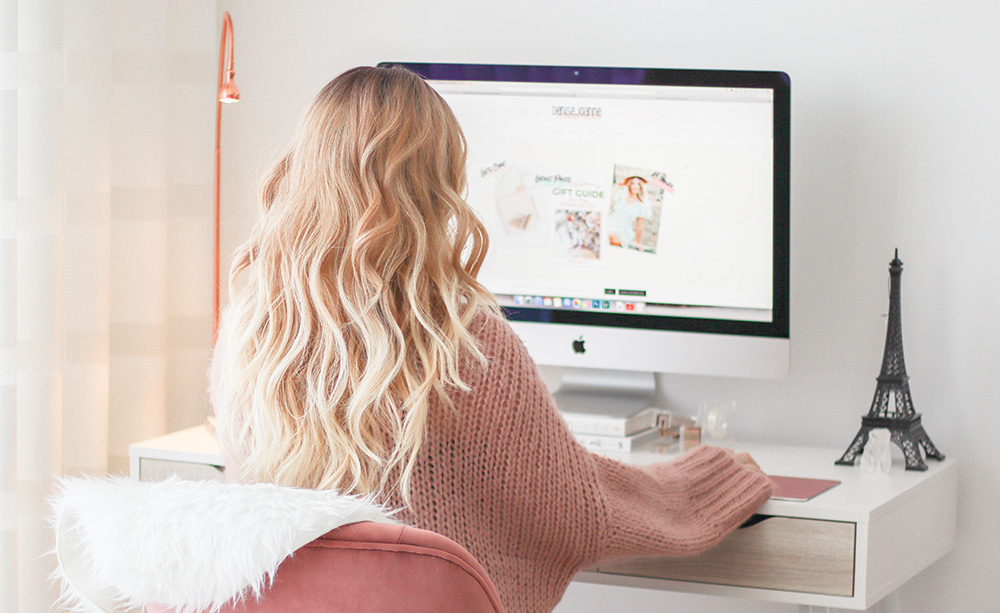 Blonde girl sitting in front of an iMac, blogging her heart out